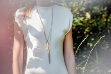 Hazy View Of Young Woman Wearing Pendant Necklace And White Top