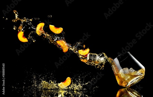Slices of peaches and cocktail splashing against black background