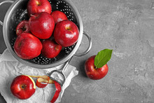 Colander With Ripe Red Apples And Peeled Fruit On Table