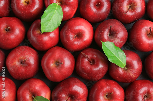 Fotografie, Obraz  Fresh ripe red apples with green leaves as background