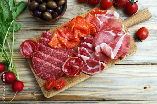 antipasto italiano con prosciutto e salame su tagliere di legno sfondo tavolo di cucina