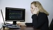 female trader talking on the phone and watching currency exchange chart at the computer monitor. Work on a crypto stock exchange
