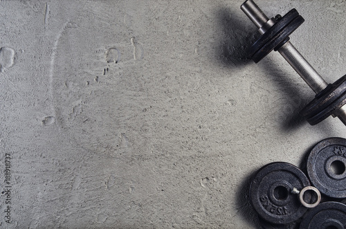 Fototapeta Fitness or bodybuilding concept background. Product photograph of old iron dumbbells on grey, conrete floor in the gym. Photograph taken from above, top view with lots of copy space obraz