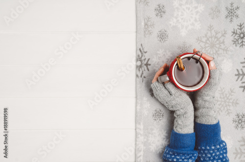 Foto op Plexiglas Chocolade Female hand holding a cup of tea or coffee on white wooden table. Winter or christmas cosy background. Photograph taken from above, top view with copy space
