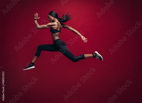 Photo Female athlete running and jumping