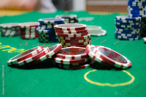 poker chips with playing cards on a green table плакат