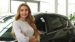 Attractive young red haired woman smiling to the camera with her arms folded posing at the dealership salon positivity buyer shopper consumerism consumables purchase rental retail sales.