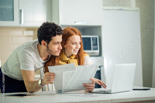 Fotografía  cheerful young couple calculating their bills at home