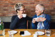 canvas print picture - Senior mother sitting in cafe bar or restauant with her middle age daughter and enjoying in conversation.