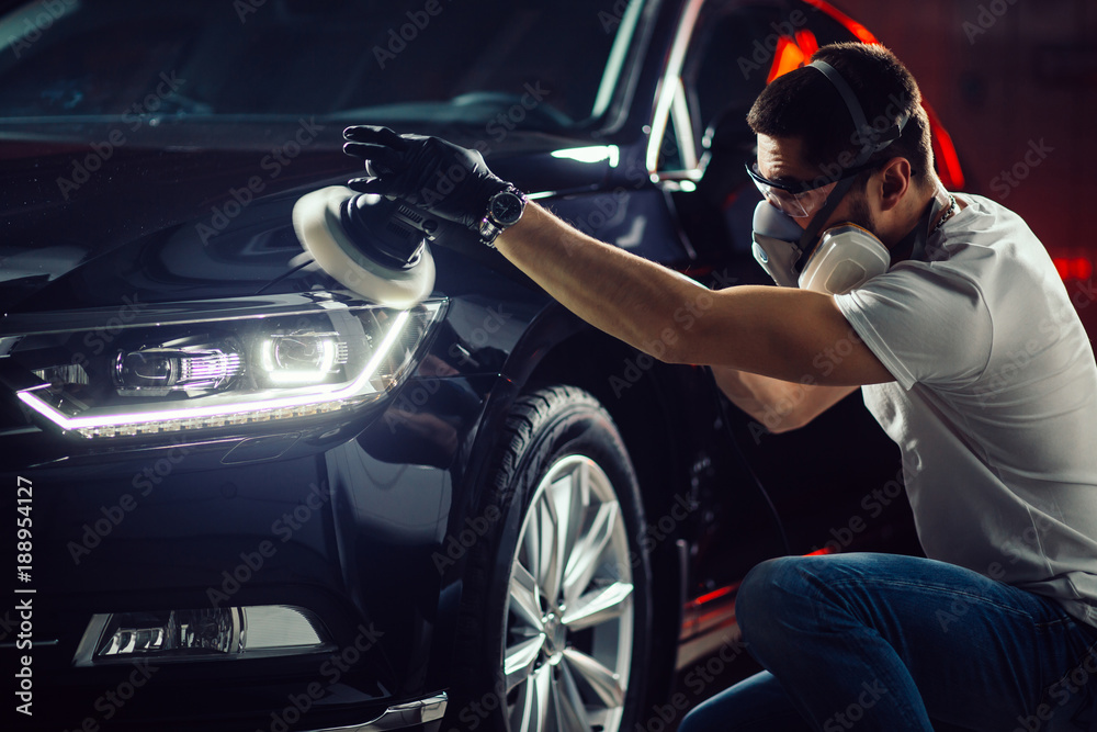 Fototapety, obrazy: Car detailing - Hands with orbital polisher in auto repair shop. Selective focus.