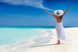 canvas print picture - Attraktive Frau in weißem Kleid läuft an einem tropischen Strand und ist glücklich