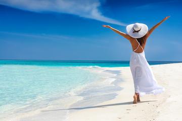 Atrakcyjna kobieta w białej sukni biegnie na tropikalnej plaży i jest szczęśliwa