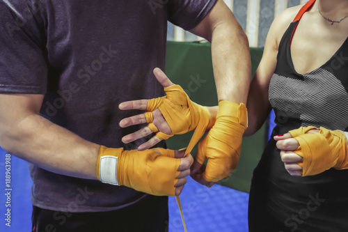 Deurstickers Vechtsport The girl's coach bandages her hands under the boxing gloves.