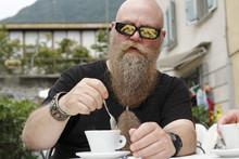 Ein Mann Mit Langem Bart Und Sonnenbrille, Genießt Eine Tasse Kaffee, Cappucino
