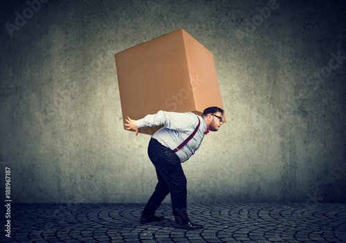 Man carrying heavy box on back