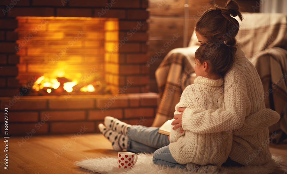 Fototapeta family mother and child hugs and warm on winter evening by fireplace.