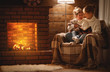 canvas print picture - happy family mother and child daughter read book on winter evening near fireplace