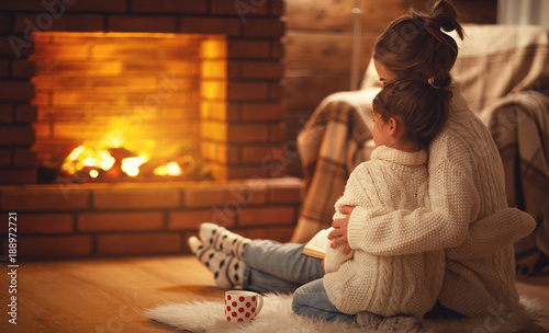 Fotografía family mother and child hugs and warm on winter evening by fireplace