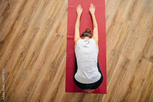Woman doing the Child's pose on red yoga mat. Balasana Poster
