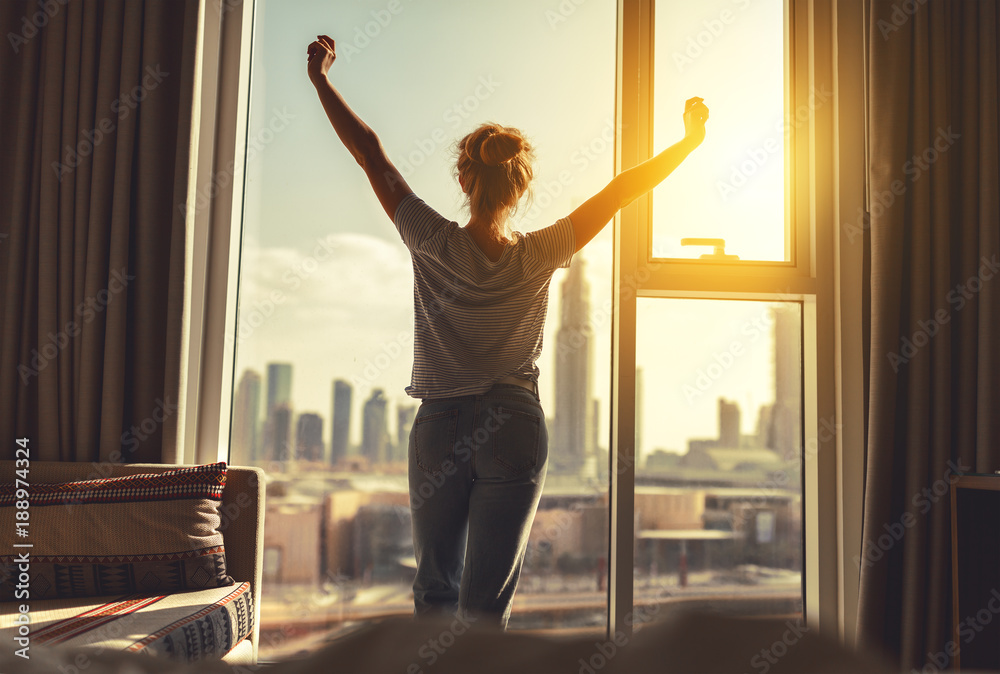 Fototapeta happy woman stretches and  opens curtains at window in morning