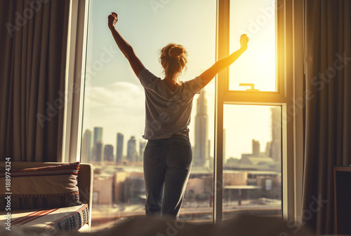 Fototapeta happy woman stretches and  opens curtains at window in morning obraz