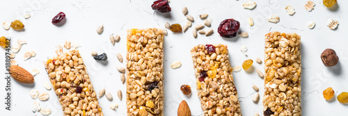 Fotografering  Granola bar with nuts, fruit and berries on white.