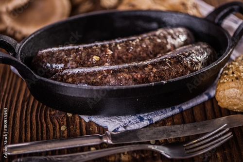 blood sausage in black cast iron baking pot on wooden table