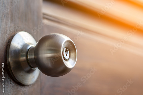 Obraz stainless door knob and keyhole on old wooden door with sunlight effect, shallow depth of field - fototapety do salonu