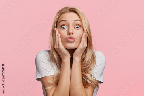 Fotografía  Pleased funny woman pouts lips and looks with bugged eyes at camera, makes grimace, has attractive look, isolated over pink background