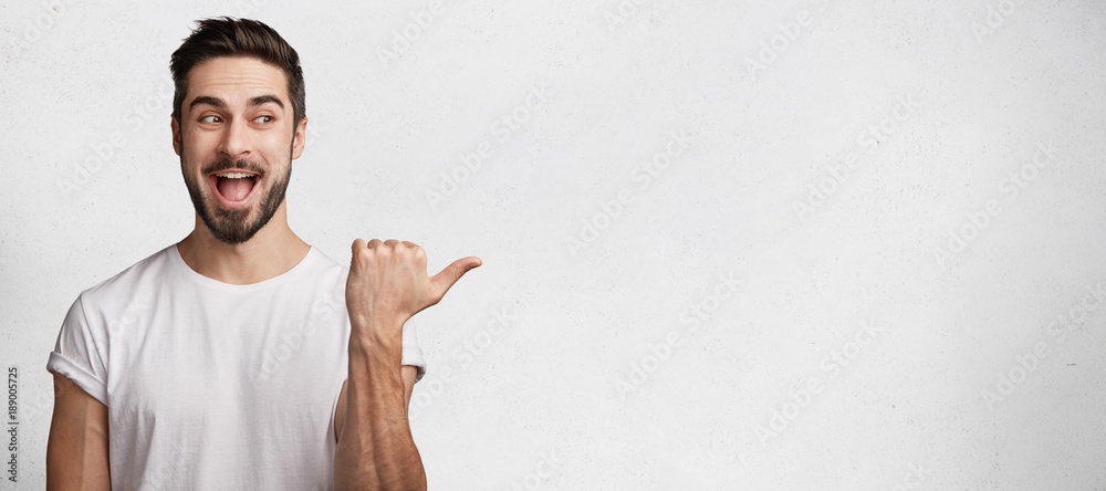 Fototapeta Horizontal shot of handsome bearded young brunet male model has appealing appearance, dressed casually, indicates with thumb aside, demostrates something excited and positive at blank copy space