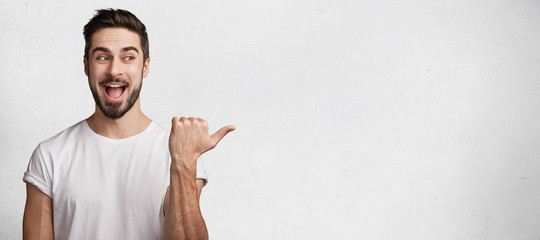 Horizontal shot of handsome bearded young brunet male model has appealing appearance, dressed casually, indicates with thumb aside, demostrates something excited and positive at blank copy space
