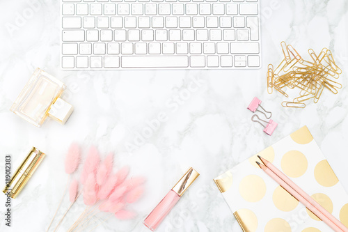 Valokuva  Blush and gold feminine desktop with makeup and keybord