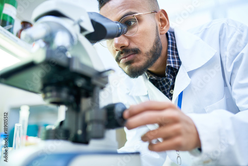 Fotografiet Portrait of young Middle-Eastern scientist looking in microscope while working o