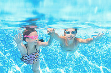 Children Swim In Swimming Pool Underwater, Happy Active Girls Have Fun Under Water, Kids Fitness And Sport On Active Family Vacation
