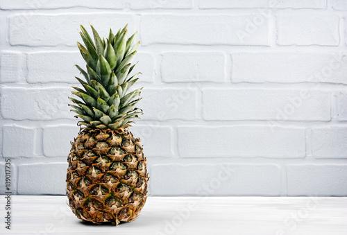 Fresh ripe whole pineapple on gray brick wall background