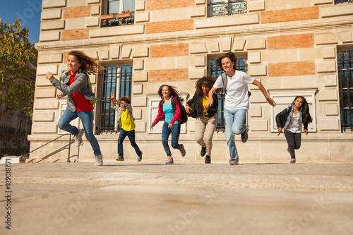 Fotografie, Tablou Happy teens running after classes at sunny day