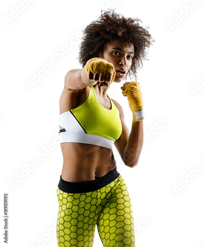 Boxer girl throwing a fierce and powerful punch. Photo of sporty african girl isolated on white background. Strength and motivation