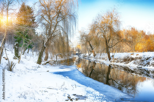 Photo sur Toile Riviere Winter landscape by a river in the sunset