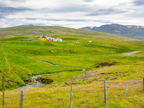 Tuinposter Pistache Icelandic landscape with green hill, mountain and a stream