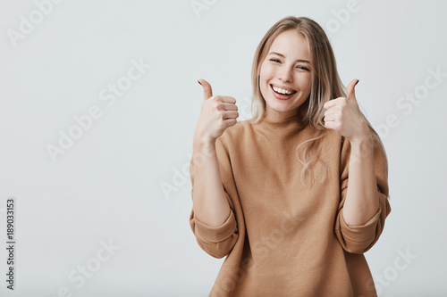 Fotografia  Portrait of fair-haired beautiful female student or customer with broad smile, looking at the camera with happy expression, showing thumbs-up with both hands, achieving study goals