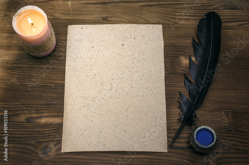 Empty blank paper page sheet with copy space, feather pen and inkstand  on wooden table background Poster