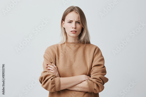 Valokuva  Waist-up portrait of beautiful girl with blonde straight hair frowning her face in displeasure, wearing loose long-sleeved sweater, keeping arms folded