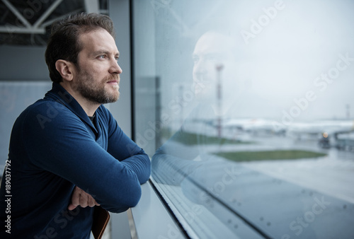 Foto  Thoughtful male person looking at the view from the window before boarding