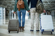 Man and woman holding each other hands while standing at the airport with big cases. Close up of their body