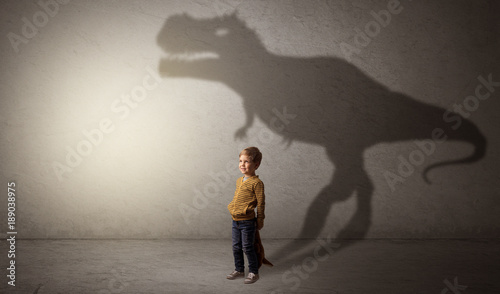 Dinosaurus shadow behind cute boy
