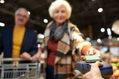Papel de parede Portrait of modern senior couple buying groceries in supermarket paying with NFC