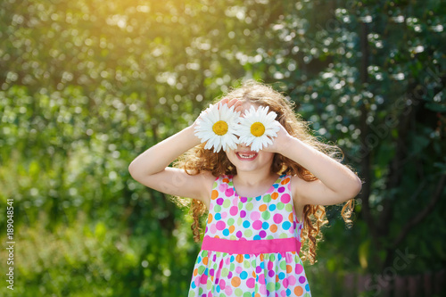Photo  Happy toothless child with daisy eyes in a spring garden.