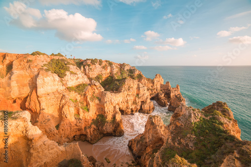 Foto op Aluminium Oranje eclat beautiful Atlantic ocean view horizon with sandy beach, rocks and waves at sunrise. Algarve, Portugal