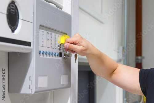 Close-up of Service Technician Opening Fire Panel In Server Room Poster