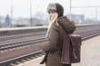woman traveler with brown leather rucksack waiting train